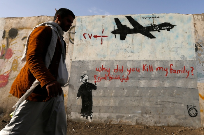 A man walks past a graffiti, denouncing strikes by U.S. drones in Yemen, painted on a wall in Sanaa November 13, 2014. Yemeni authorities have paid out tens of thousands of dollars to victims of drone strikes using U.S.-supplied funds, a source close to Yemen's presidency said, echoing accounts by legal sources and a family that lost two members in a 2012 raid. REUTERS/Khaled Abdullah (YEMEN - Tags: CIVIL UNREST MILITARY POLITICS SOCIETY TPX IMAGES OF THE DAY) - RTR4E1VF